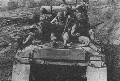 Infantrymen mounted on medium tank, M4A1.