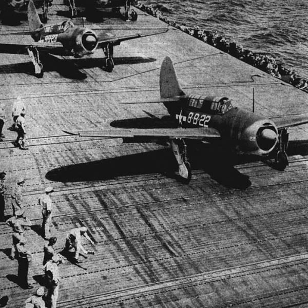 Helldivers on a carrier roll forward to take off.