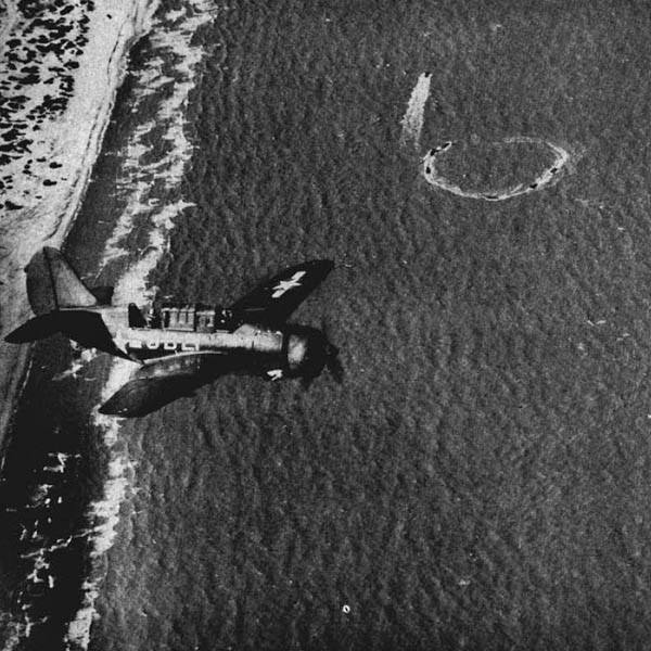 A Helldiver roars low over the shore as landing craft in maneuvers whirl through their buzzsaw circles before shooting toward the beach.