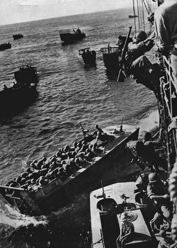 U.S. troops go over the side of a Coast Guard-manned combat transport to enter landing craft for the invasion of Empress Augusta Bay, Bougainville.  (Official U.S. Coast Guard Photograph.)